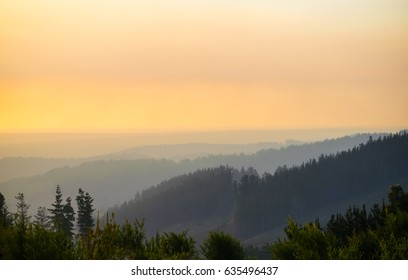 Late afternoon colour with hills receding into haze and forested hills in foreground