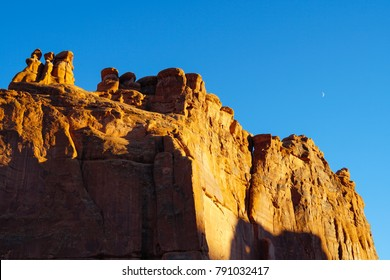 Late Afternoon and a crescent moon add to the amazing beauty of Arches National Park's stone walls.