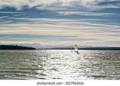 Late afternoon at a lake called Ammersee with a sail boarder and the peaks of the bavarian alps in the background, Bavaria, Germany