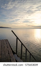 Late afternoon at a lake called Ammersee with a wooden landing pier and with the bavarian alps in the background, Bavaria, Germany