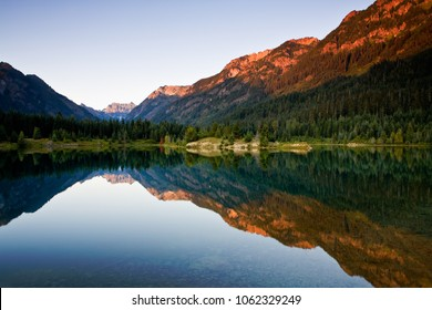 Late afternoon light catches the peaks of the surrounding mountains above Gold Creek Pond in the Cascade Mountains of Washington state