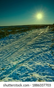 Late afternoon, and a low sun lights up a snowy moorland track in Yorkshire