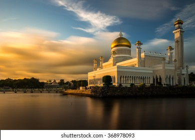 The late afternoon sun sets over Bandar Seri Begawan, Brunei, and strikes the facade of the Sultan Omar Ali Saifuddin Mosque.