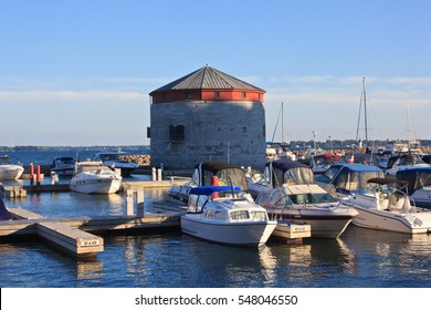 Late afternoon sunlight casts a warm glow on the marina and historic stone Martello tower fort in Kingston, Canada.