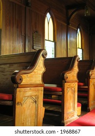 late afternoon sunlight falls across old cypress pews in a small town American church buillt in the early 1830s