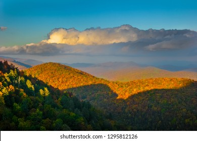 The late afternoon sunlight shines on the Autumn forest as well as the fluffy clouds on the Blue Ridge Parkway in North Carolina.