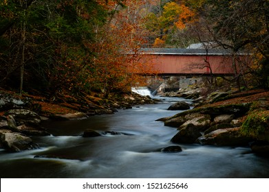 A late autumn view of the historic red painted McConnells Mill Covered Bridge, a covered Howe truss, within the scenic McConnells Mill State Park in the Appalachian Mountains of western Pennsylvania.