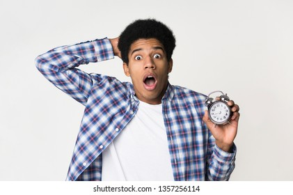 Late to college. Shocked guy holding alarm clock over light background