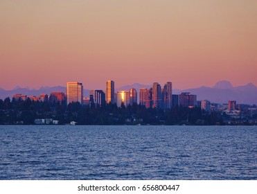 Late day sun shines on the downtown buildings of Bellevue, Washington with a pinkish dusk sky & some of the Cascade Mountains in view in this look across Lake Washington from Seattle.