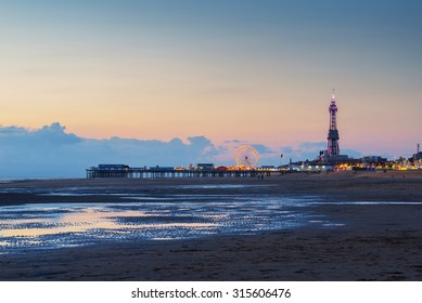 Late evening after sunset in Blackpool beach ,England, UK. Pier with attraction in background.