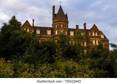 A late evening / blue hour view of the Main Building surrounded by yellow goldenrods at the long abandoned Hudson River State Hospital in New York.