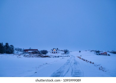 Late evening shot of remote farm surrounded with snow in winter, Iceland. Cold winter evening in Icelandic countryside.