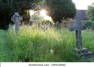 Late evening sun shines through trees to headstones in a church yard Oakley Hampshire