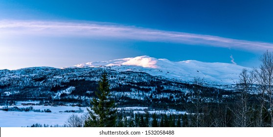 Late evening sunset in winter Lappland Mountains in Northern Sweden - frozen lake with fir and bjork in the in the wild forest, old airplane trace across whole sky, rose colored snow at mountain tops