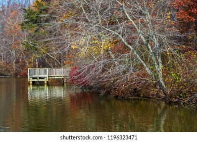 A late Fall landscape with changing leaves and reflections on the lake.