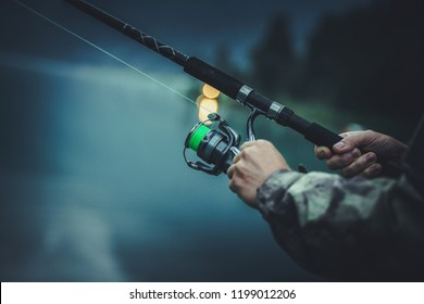 Late Fly Fishing. Angler with Fishing Rod in Hands. Closeup Photo.