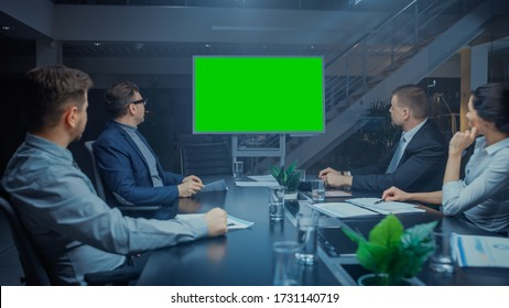 Late at Night In Corporate Meeting Room: Board of Directors, Executives and Businesspeople Sitting at Negotiations Table, Talking and Using Green Mock-up Screen Wall TV for Video Conference Call.