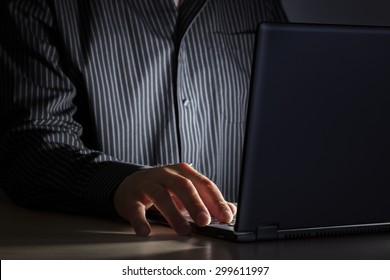 Late night internet addiction or working late man using laptop at a desk in the dark