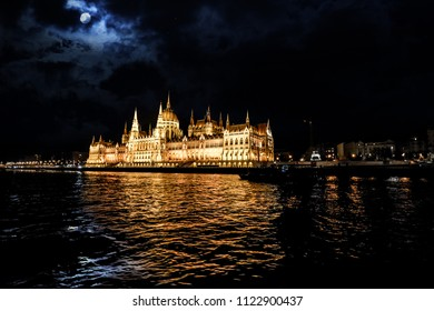 Late night on the Danube River with a tour boat alongside the Budapest Parliament Building, with a full moon behind and bats flying above the dome