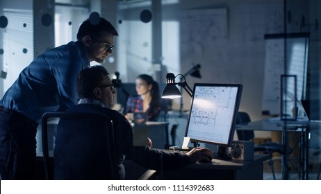 Late at Night Two Men Discuss Blueprints that are Shown on Display of a Personal Computer. Office Looks Modern with Lots of Blueprints on the Walls. In the Background Woman Working.