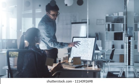 Late at Night/Early Morning in the Office, Male and Female Engineers Discuss  Blueprints Shown on Her Display. Office Looks Modern, with Blueprints on Walls.