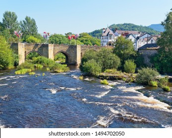 Late on a hazy summer afternoon the fast flowing River Dee flows through the old stone bridge, draped in bunting and flags, in Llangollen, Wales