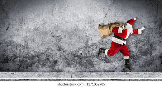 late Santa claus in a hurry with traditional red white costume and bag full of presents running jumping abstract funny christmas xmas concrete background with copy space