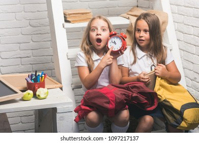Late. Shoked small girls show time on clock. small kids late to school.