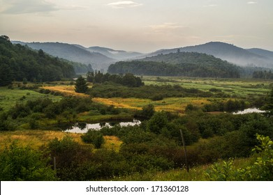 Late summer in the Adirondack Mountains in New York with a swampy foreground and fog in the background mountains.
