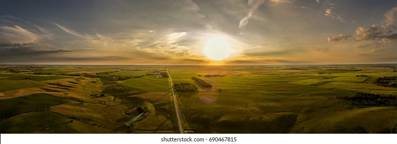 A late Summer cloudy sunset panoramic above a country road in the Midwest sate of South Dakota.