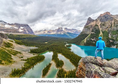 Late Summer hiker on top of Opabin Prospect overlooking Lake O'Hara and Mary Lake with the Canadian Rockies in the background surrounded by Wiwaxy Peaks and Odaray Mountain