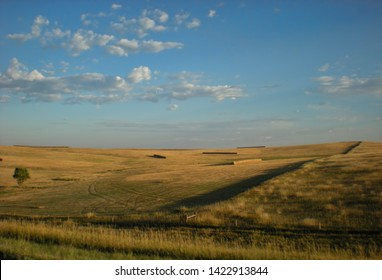 Late summer scene of a prairie landscape with cylindrical bales of hay. Beautiful blue sky with fair-weather clouds.