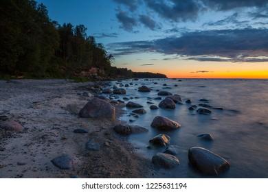 Late sunset view of rocky sea coast. Estonia. Long exposure.