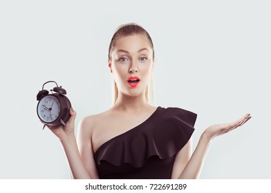 I am late, what to do now? Portrait of young surprised woman with alarm clock on white light blue background