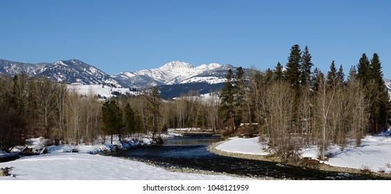 Late winter view of Methow River with Mt. Gardner in background under a blue sky - wide shot