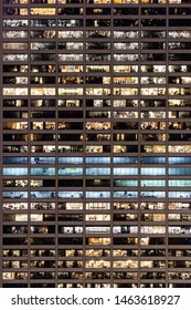 Late Working urban concept, window facade of business center office building at night, New York city NY USA