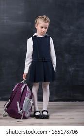 Latecomers little schoolgirl with backpack near blackboard