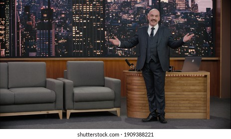 Late-night talk show host is performing his monologue, looking into camera. TV broadcast style show.