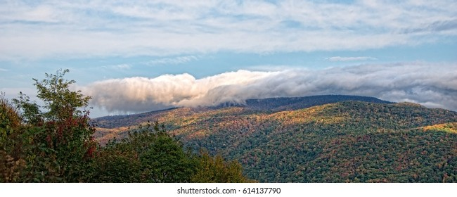 Later afternoon clouds rolling over the mountains in late fall with shadows and bright fall colors