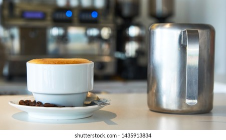 Lateral view. Cafeteria coffee shop restaurant. Cafe latte in white textured surface. Porcelain mug and plate. Creamy milk brown toasted coffee beans espresso. Workplace context iphoto. Metallic jar.