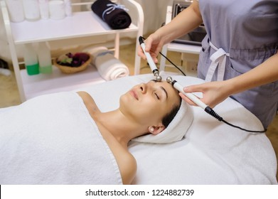 Lateral view of woman facial massage spa procedure. Electric stimulation facial skin care. Microcurrent lift face. Beauty spa procedure. Anti aging rejuvenation non surgical treatment in medical room