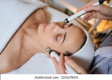 Lateral view of woman facial massage spa procedure. Electric stimulation facial skin care. Microcurrent lift face. Beauty spa procedure. Anti aging rejuvenation non surgical treatment in medical