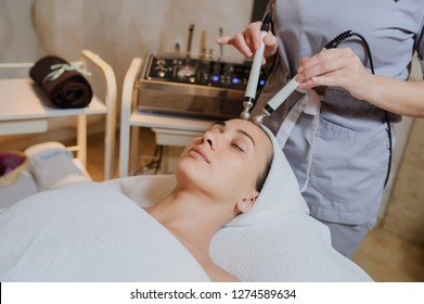 Lateral view of woman facial massage spa procedure. Electric stimulation facial skin care. Microcurrent lift face. Beauty spa procedure. Rejuvenation non surgical treatment in medical interior room