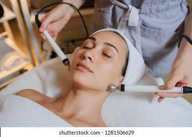 Lateral view of woman facial massage spa procedure. Electric stimulation facial skin care. Microcurrent lift face. Beauty spa procedure. Anti aging rejuvenation non surgical treatment i