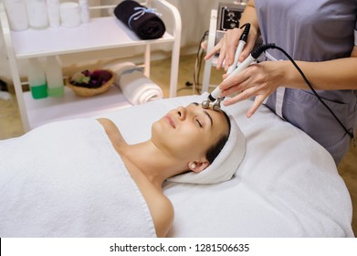 Lateral view of woman facial massage spa procedure. Electric stimulation facial skin care. Microcurrent lift face. Beauty spa procedure. Anti aging rejuvenation non surgical treatment