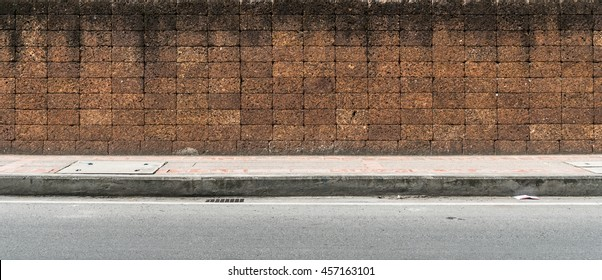 Laterite block fence and concrete sidewalk and asphalt road