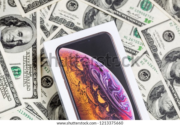 Latest Iphone XS in unopened box on US dollar banknotes background.