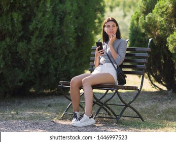 Late-teens girl at the park. Eighteen-year-old girl sitting on a bench in the park and talking on a smartphone
