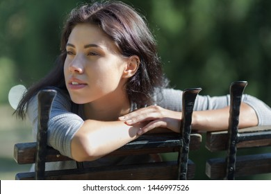 Late-teens girl at the park. Eighteen-year-old girl sitting on a bench in the park and looking away