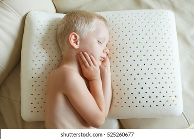 latex pillow texture; perforated natural latex; hevea juice; orthopedic. Little boy resting his head on natural latex pillow, sleeping